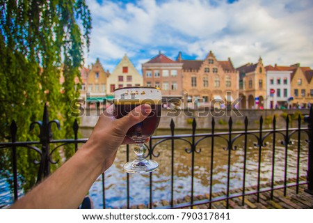Full glass of beer on Brugge cityscape background. Hand with beer glass in Bruges, Belgium. #790317841
