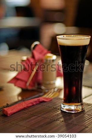 Full glass of dark beer at the wood cafe table