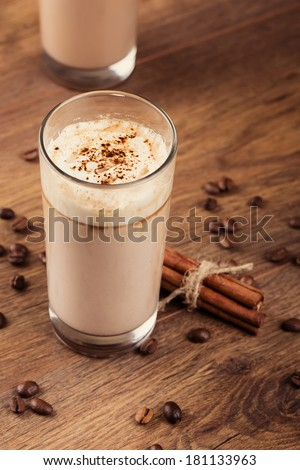 Full glass of milk cocktail and coffee beans on the wooden background #181133963