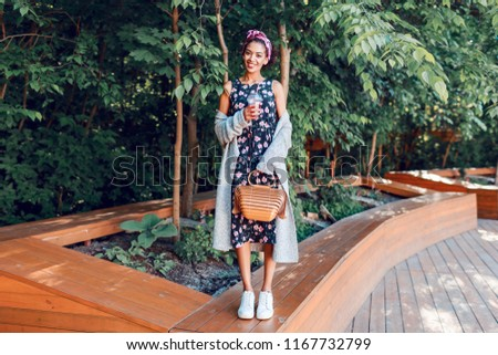 Full height image of   black woman in stylish hipster clothes grey cardigan walking in sunny park and enjoying   weekends, Trendy bamboo bag .  Drinking lemonade.
