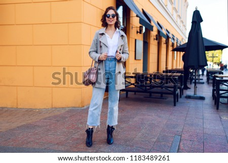 6665936dace9 Full height image of stylish pretty girl in autumn coat walking outdoor in  the city.