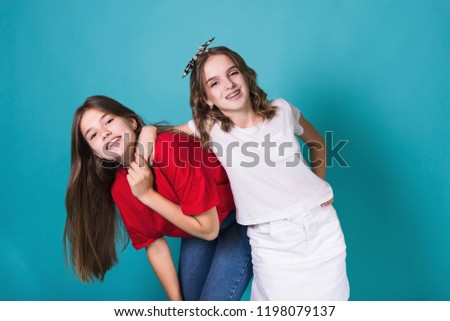 Full height image of two happy cheeky girls , best friends having fun , laughing on blue background. . Wearing stylish casual clothes. Space for text. Cute teenage school girls