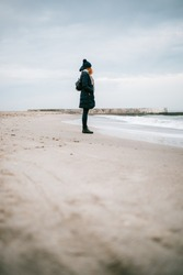 Full height lonely young woman standing on deserted beach looking at tidal waves on cloudy winter day.