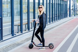 Full height photo of blond woman in black eyeglasses and wearing black clothes riding electric scooter on empty city street.Eco-friendly transport. Safety concept for road users. Rent scooter.