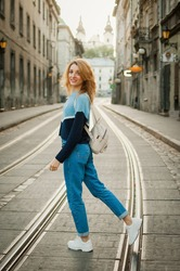Full height portrait of young woman in blue casual sweater, jeans, white shoes, and small backpack early in the morning in ancient city in Europe on empty street with tramway background.