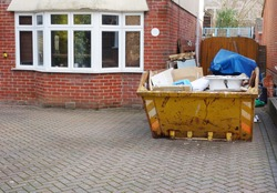 Full industrial rubbish bin on driveway in front of brick house with space to add text for background use, on side of heavy skip, pavement floor. Renovate, removal, recycle & home clearance concept.