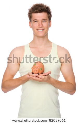 Full isolated portrait of a  smiling young man with piggybank