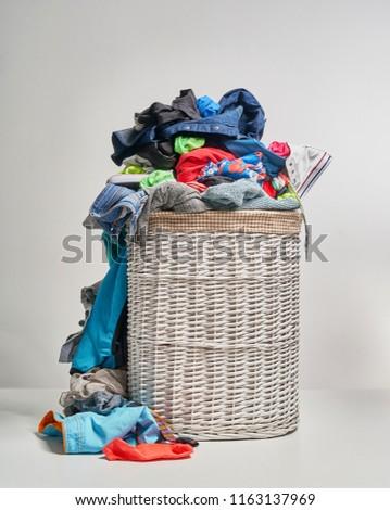 Full laundry white wicker basket on the grey background