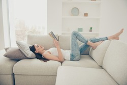Full legs body size glad positive grinning cheerful charming lady with her white toothy hollywood smile she lay in comfort modern light house in denim jeans at couch sofa in living room read book