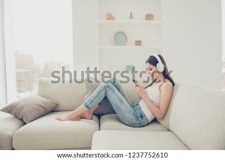 Full legs body size lady with her cellular in hands she sit on couch sofa comfort modern light house living room search best melody or song enjoy favorite audio mp3 track sound playlist
