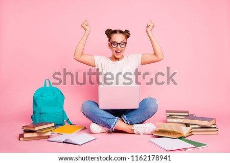 Full legs, body, size portrait of reader girl in blue jeans and white t-shirt with a laptop on her knees raises her fists up and joyfully shouts cheers isolated on bright pink background