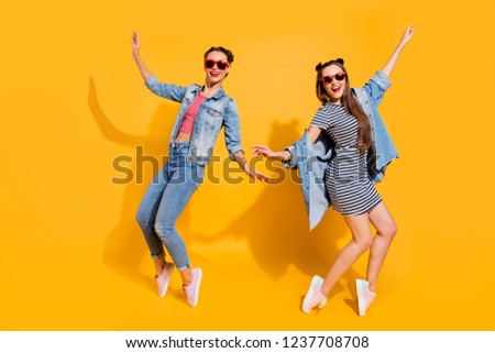 Full legs length body size portrait of two adorable good-looking brunette hair lady in glasses spectacles raised hands up make beaming hollywood smile dance isolated on yellow shine background