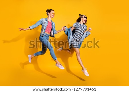 Full legs length body size portrait of two sweet gorgeous adorable good-looking funky funny crazy lady in glasses spectacles hold by hand each other run away isolated on yellow shine background