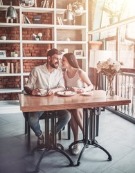 Full-lenght image of beautiful couple in love is sitting in cafe. Happy young man is listening to his woman whispering on ear and smiling.