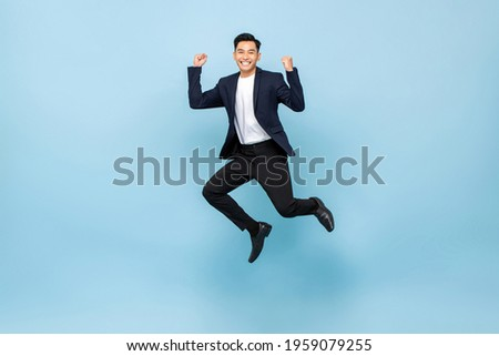 Full lenght portrait of smiling handsome Asian man jumping and raising  his fists on isolated light blue studio background Сток-фото ©