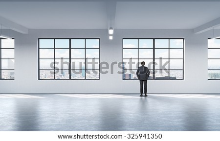 Full length a man in formal suit who is looking out the window in New York, modern loft style open space.