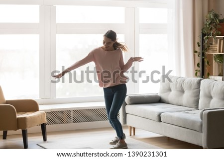 Full-length active young woman in casual clothes turn music on dancing moving in living room stands near window cozy modern interior sunny summer day, celebrating event, feels happy enjoy life concept