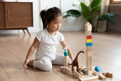 Full length adorable interested small asian vietnamese ethnicity preschool baby girl sitting on warm wooden floor, playing with colorful wooden cubes constructing building alone in living room.