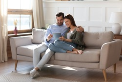 Full length affectionate young man embracing attractive wife girlfriend, looking at digital computer tablet screen, relaxing on comfortable couch. Loving couple shopping online in internet store.