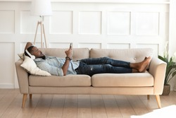 Full length african man lying down on comfy couch in modern cozy light living room take break listens music on headphones, man resting indoors hold smartphone watching video enjoy lazy weekend concept