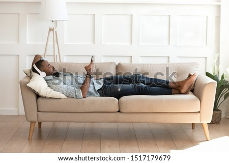 Full length african man lying down on comfy couch in modern cozy light living room take break listens music on headphones, man resting indoors hold smartphone watching video enjoy lazy weekend concept Foto d'archivio ©