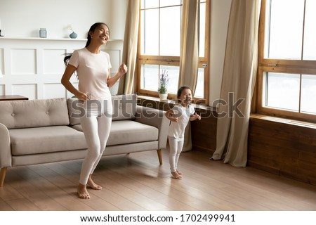 Full length asian happy mother little daughter in casual comfort clothes standing barefoot on warm wooden floor in sunny living room enjoy life, listen music dancing, having fun at modern home concept
