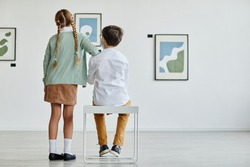 Full length back view at boy and girl looking at paintings in art gallery, copy space