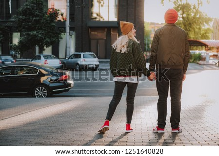 Full length back view portrait of charming girl standing with boyfriend on sidewalk. She is looking at him and smiling