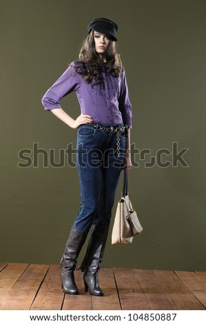 Full length beautiful fashion woman in hat with bag posing wooden floor