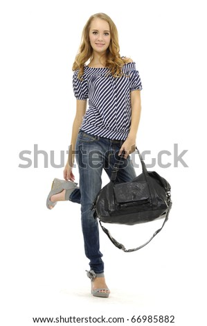 Full length beautiful fashion woman in jeans with bag posing