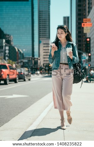 full length beautiful smiling asian woman office lady walking on crowded city street from work with coffee cup and texting on mobile phone. elegant young businesswoman in traffic area by foot commute