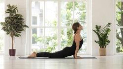 Full-length beautiful woman in black activewear practising yoga asana near window at sunny summer morning do Urdhva Mukha Svanasana Upward Facing Dog stretches chest and spine, relief fatigue concept