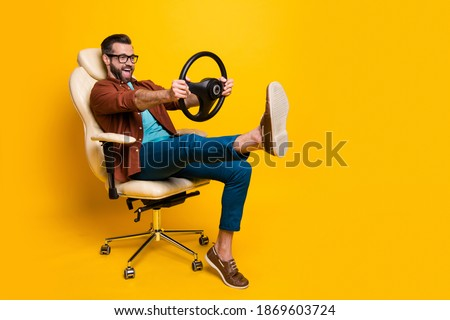 Full length body photo of happy fooling man in chair keeping steering wheel pretending car driver isolated vivid yellow color background