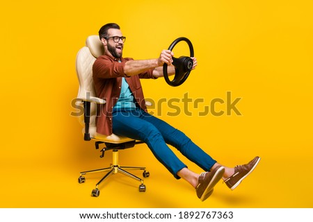 Full length body photo of playful crazy man in chair holding steering wheel pretending car rider isolated vivid yellow color background Stock photo ©