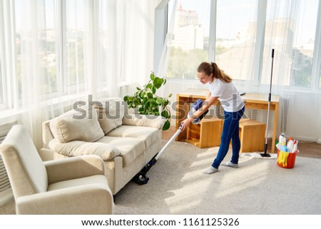 Full length body portrait of young woman in white shirt and jeans cleaning carpet with vacuum cleaner in living room, copy space. Housework, cleanig and chores concept #1161125326