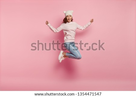 Full length body shot of joyful pleased young female model jumps happily in air against pink background, wears warm hat with ears, sweatshirt, jeans and sneakers, feels energetic and optimistic #1354471547