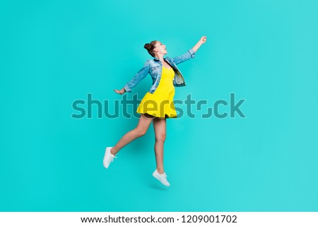 Full length body size of nice crazy positive childish comic girl with hair-buns, wearing short dress and denim jacket, flying, showing like holding umbrella, isolated on green turquoise background