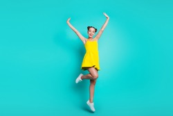 Full length body size of nice cute cheerful positive glad trendy attractive charming girl with hair-buns, dancing in short dress, raising hands up isolated on green turquoise background