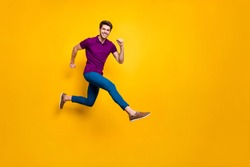 Full length body size phoo of cheerful brown haired attractive man wearing blue pants trousers purple t-shirt footwear aspiring jumping running isolated over yellow vivid color background