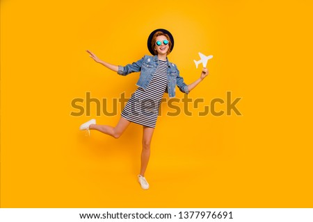Full length body size photo beautiful foxy she her lady paper airplane traveler imagine flight wear specs vintage hat casual striped t-shirt dress jeans denim isolated yellow bright vivid background #1377976691