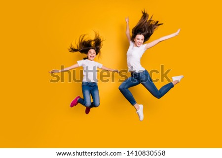 Full length body size photo beautiful her she diversity different age lady weekend mood spend free time together jump high hair flight wear casual white t-shirts jeans denim isolated yellow background