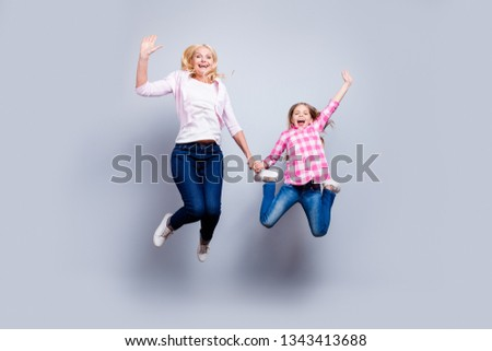 Full length body size photo blond haired she her little mature granny waving hands jump high achievement wear casual shoes jeans plaid checkered shirt sweater outfit clothes isolated grey background