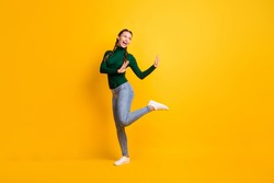 Full length body size photo childish girl dancing laughing looking blank space isolated on vibrant yellow color background