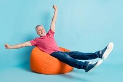 Full length body size photo elder man laying chilling on working break on beanbag overjoyed isolated pastel blue color background
