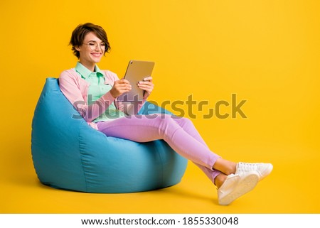 Full length body size photo female student glasses using tablet reading article in internet isolated on vibrant yellow color background