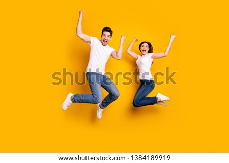Full length body size photo funky she her he him his pair jumping high raised fists yell scream shout loud cheerleader football fans wear casual jeans denim white t-shirts isolated yellow background #1384189919