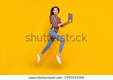Full length body size photo girl in casual clothes jumping browsing internet on laptop isolated bright yellow color background