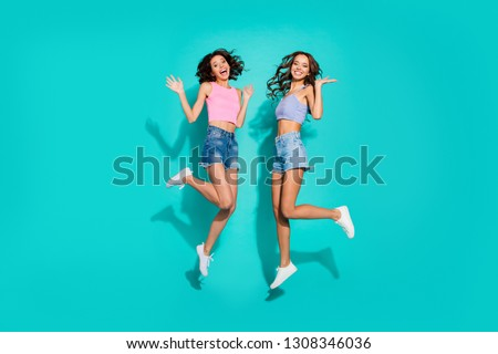 Full length body size photo jumping beautiful two funky wavy she her ladies hands arms raised in hi gesture friendly wearing shiny jeans denim shorts tank tops isolated teal bright vivid background #1308346036