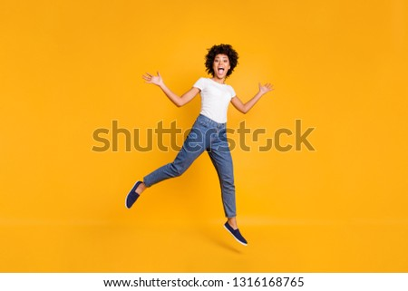 Full length body size photo jumping high beautiful she her lady like comedian actor playful active energetic wearing casual jeans denim white t-shirt clothes isolated yellow background