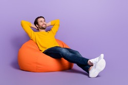 Full length body size photo man laying in beanbag chilling dreamy looking copyspace isolated pastel purple color background